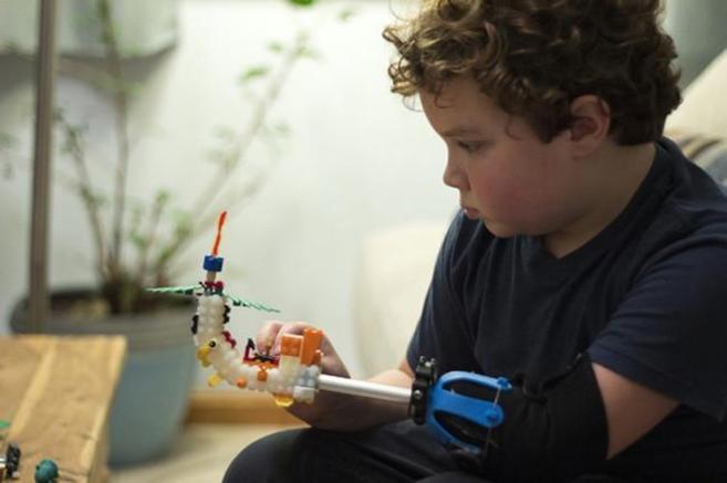 Foto de Aidan Robinson que ha creado, a sus 9 años, una prótesis con piezas de lego útil para desarrollar todo tipo de actividades